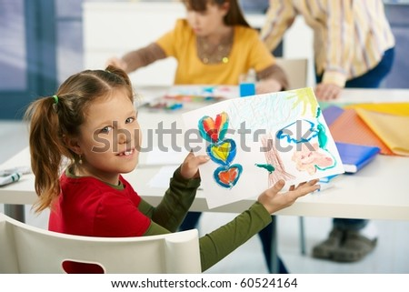 Portrait of elementary age schoolgirl showing colorful paining to camera in art class in primary school classroom.? - stock photo