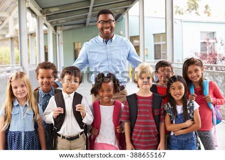 Portrait of elementary school kids and teacher in corridor - stock photo