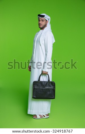 Portrait of Emirati businessman holding bag - stock photo