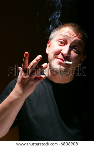 Portrait of emotional man with cigarette over black background - stock photo