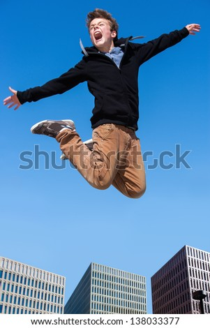 Portrait of euphoric boy jumping high in city. - stock photo