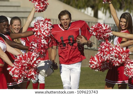 Portrait of excited american football player with cheerleaders cheering for him - stock photo
