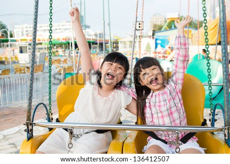 Portrait of excited friends sitting on swings in an amusement park - stock photo