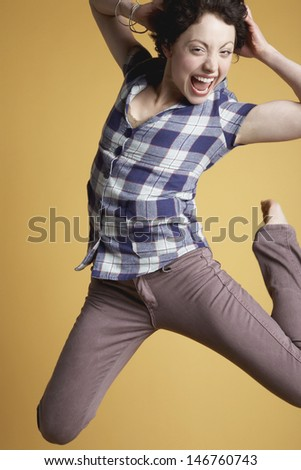 Portrait of excited young woman jumping and screaming on orange background - stock photo
