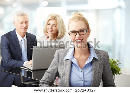Portrait of executive businesswoman sitting at office while business people working on laptop in background. Teamwork at business meeting.  - stock photo