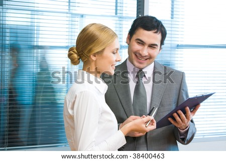 Portrait of executive employees looking at document in male hand and discussing it in office - stock photo