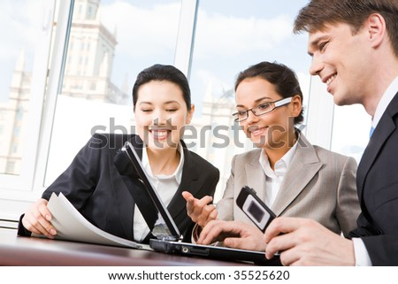 Portrait of executive employees looking at laptop monitor and discussing new project during meeting - stock photo