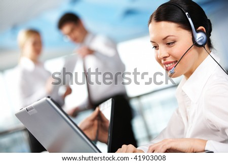 Portrait of executive female in headset working on background of communicating partners - stock photo