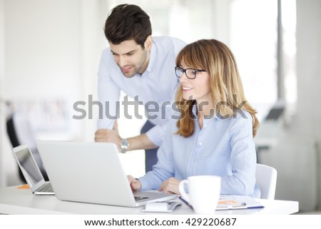 Portrait of executive financial businesswoman and her young assistant using laptop while discussing the new business plan. - stock photo