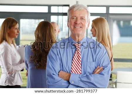 Portrait of executive manager standing at office while colleagues consulting at background. Teamwork at office. - stock photo