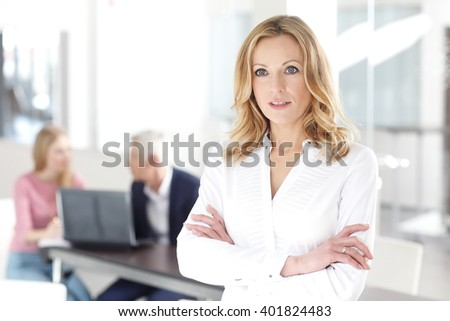Portrait of executive middle aged businesswoman standing at office while her colleagues consulting at background.  - stock photo