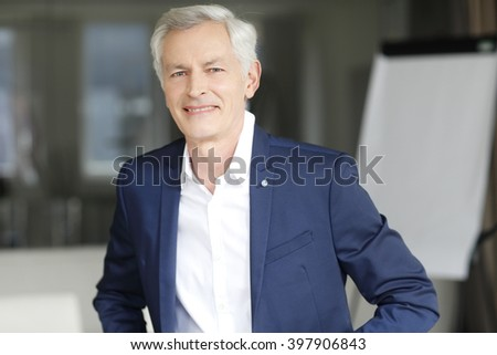 Portrait of executive senior businessman sitting at office and working.  - stock photo