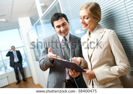 Portrait of executive specialists looking at document and discussing it - stock photo