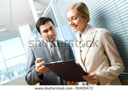 Portrait of executive specialists looking at document in female hand and discussing it in office - stock photo