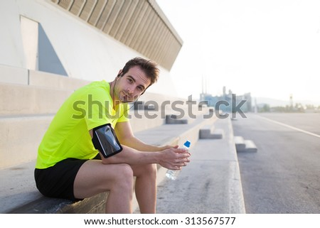 Portrait of exhausted male runner enjoying a rest after intensive fitness training outdoors, caucasian sports man holding bottle of water and look at you with copy space area for your text message - stock photo