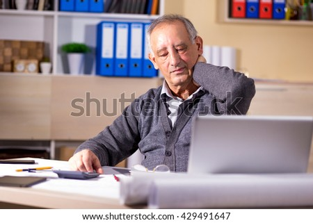 Portrait of exhausted senior businessman working in his office. - stock photo