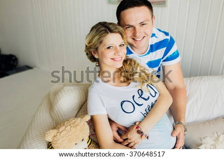 Portrait of expecting couple laughing happily at camera, embracing baby in belly together. Couple dressed in blue and white colors. - stock photo
