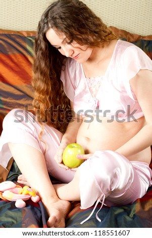 Portrait of expecting mother  Caucasian pregnant  woman in pink lingerie with long hair and apple on bed at home - stock photo