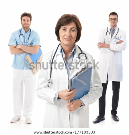 Portrait of experienced female doctor smiling, young male doctors standing behind. - stock photo