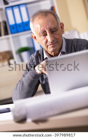 Portrait of experienced senior businessman working on laptop in his office. - stock photo