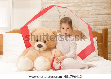 Portrait of expressive beautiful little girl sitting in bed under umbrella with her teddy bear. Security concept - stock photo