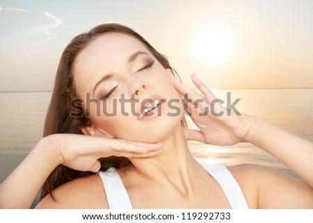 Portrait of expressive beautiful woman against sea sunset - stock photo