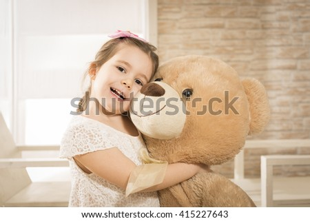 Portrait of expressive charming little girl hugging huge plush bear, indoor shot. Little girl playing with teddy bear - stock photo