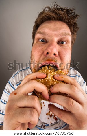 Portrait of expressive fat man chewing hamburger - stock photo