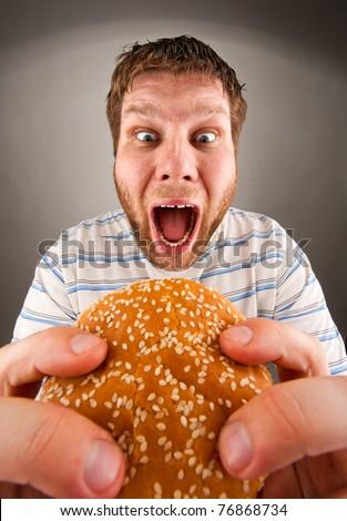 Portrait of expressive man eating juicy hamburger - stock photo