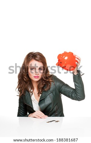 Portrait of expressive young brunette woman with her piggy bank. - stock photo