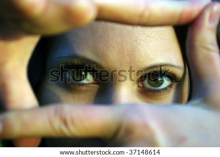Portrait of eyes looking through fingers frame - stock photo