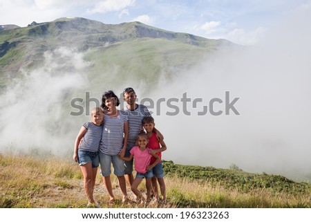 Portrait of family at cloudy Pyrenees mountain background. Andorra - stock photo