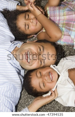 Portrait of family, dad playing with their children at home - stock photo