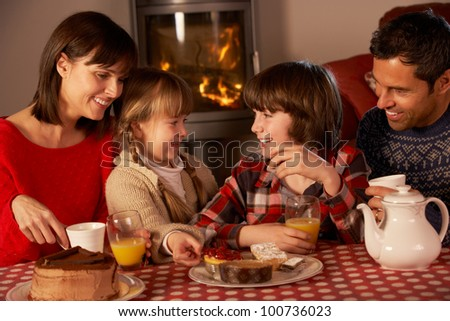 Portrait Of Family Enjoying Tea And Cake By Cosy Log Fire - stock photo
