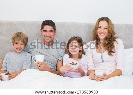 Portrait of family having breakfast together in bed - stock photo