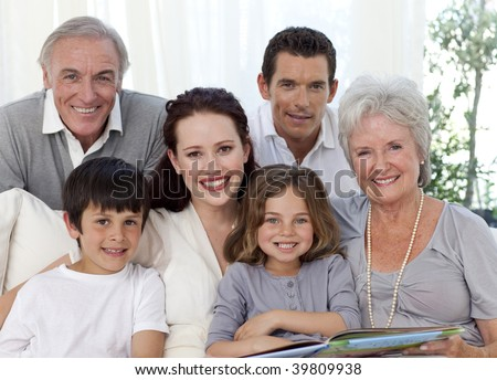 Portrait of family looking at a photograph album at home - stock photo