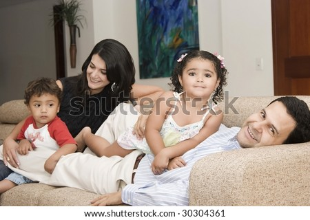 Portrait of family, mom and dad playing with their children at home - stock photo