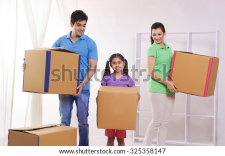 Portrait of family moving into new home - stock photo