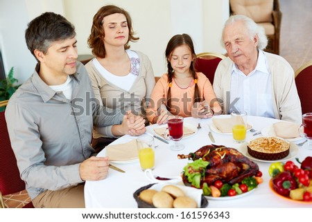 Portrait of family of four sitting at festive table and praying - stock photo