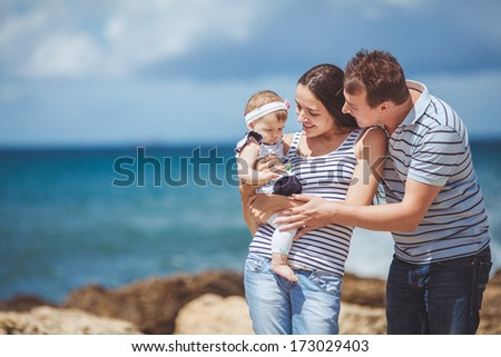portrait of family of three having fun together by the ocean shore and enjoying the view. Outdoors - stock photo