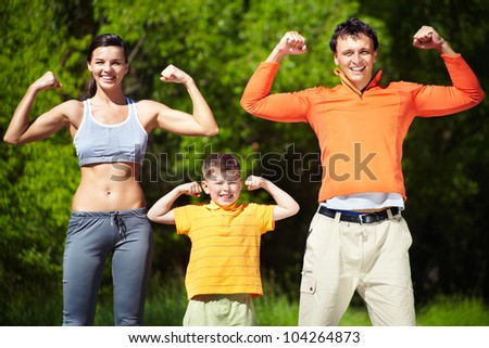 Portrait of family of three showing their strength - stock photo