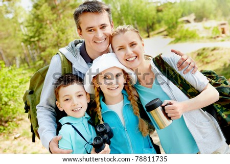 Portrait of family of travelers looking at camera in summer - stock photo