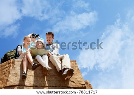 Portrait of family of travelers sitting on rocky cliff and looking at map - stock photo