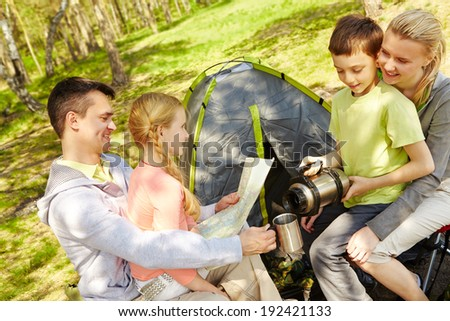 Portrait of family of travelers spending time in forest with tent near by - stock photo
