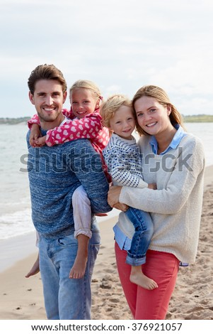 Portrait Of Family On Beach Vacation Walking By Sea - stock photo