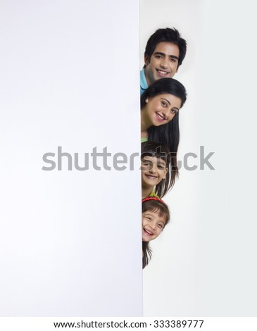 Portrait of family peeking behind white board - stock photo