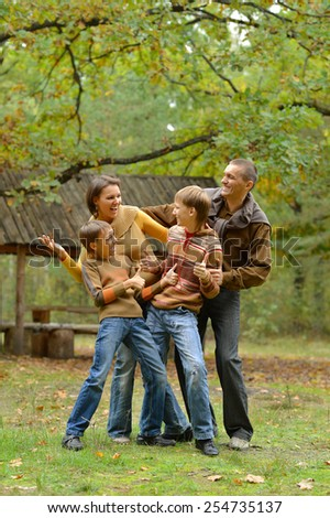 Portrait of family relaxing in autumn park - stock photo