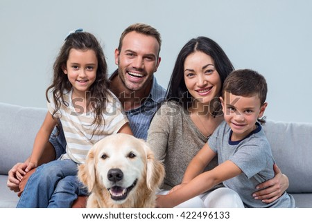 Portrait of family sitting on sofa with dog in living room - stock photo