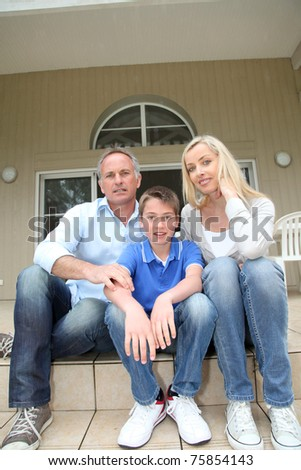 Portrait of family sitting on the front door stairs - stock photo