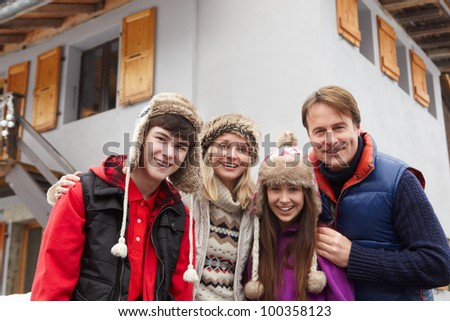Portrait Of Family Standing Outside Chalet On Ski Holiday - stock photo